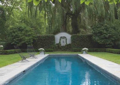 SWIMMING POOLS: Formal shaped hedge garden with narrow pool , bluestone patio, white flowers in grey containers, straight on view with NO  curved edge of patio to camera